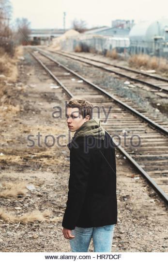 Junger Mann zu Fuß entfernt, in der Nähe von Eisenbahnschienen Stockbild