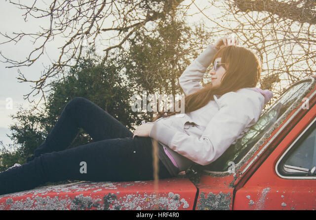 Junge Frau in einem Retro-Auto liegend Stockbild