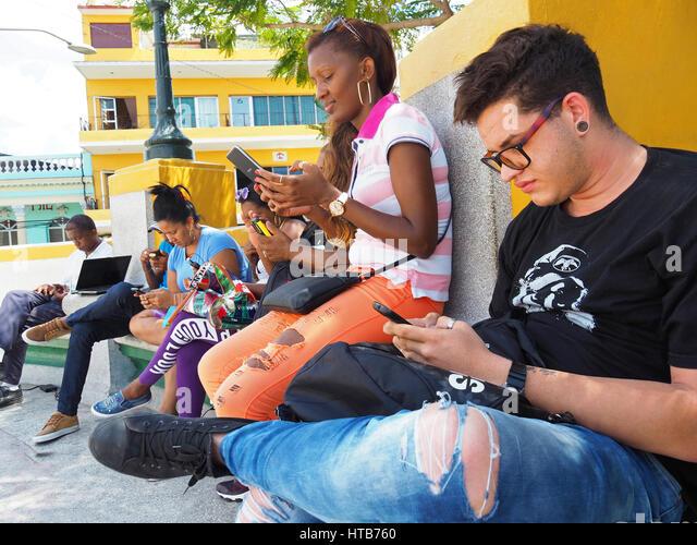 Junge Kubaner in Santiago De Cuba Marti Plaza konzentriert sich auf die Verwendung von Smartphones. Stockbild