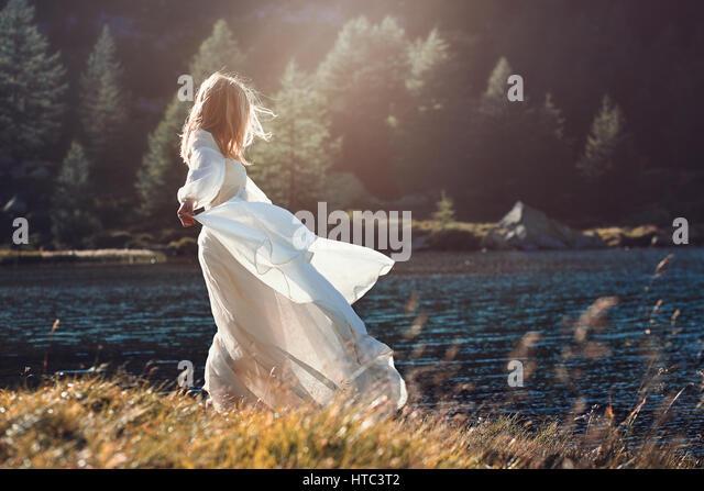 Romantische Vintage Frau im Abendlicht. Alpensee Hintergrund Stockbild