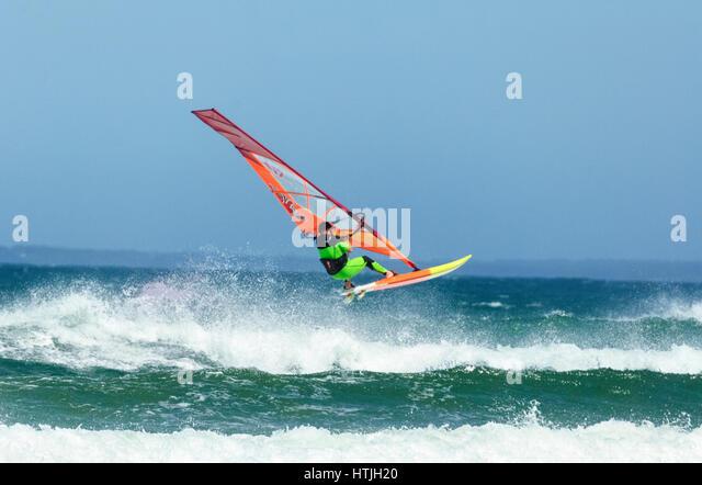 Windsurfer springen über eine große Welle am Seven Mile Beach, Gerroa, Illawarra Coast, New-South.Wales, Stockbild
