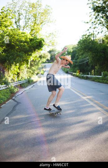 Junge Skateboard auf der Straße Stockbild