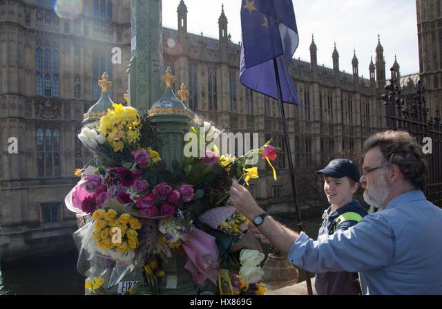 London UK 25. März 2017A Mann und seinem Sohn Blätter floral Tribute zu Ehren der Opfer der Londoner Terror Stockbild