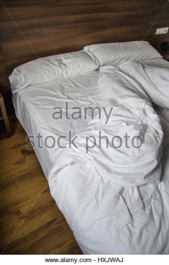 Detail auf einem unordentlichen Bett mit zerknitterten Bettwäsche Stockbild