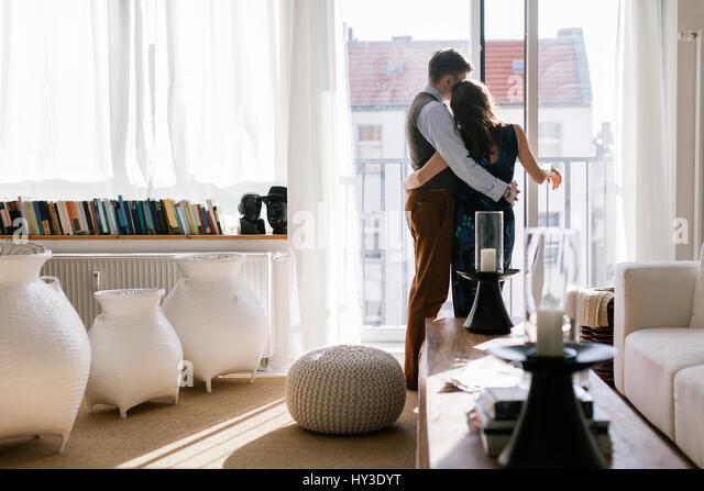 Deutschland, Paar umarmen durch Fenster im Wohnzimmer Stockbild