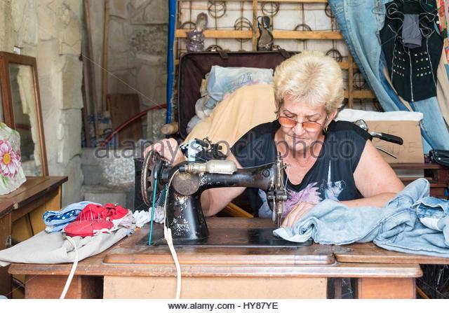 Kubanische selbst beschäftigte Näherin Frau Nähen alte Kleidung oder neue zu schaffen in ihrem Haus Stockbild