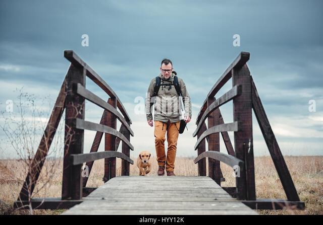 Wanderer und Hund überqueren Holzbrücke am bewölkten Tag Stockbild