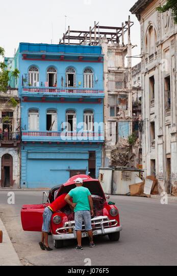 Zwei kubanische Männer reparieren ihr Auto mitten auf der Straße in Alt-Havanna, Kuba. Stockbild