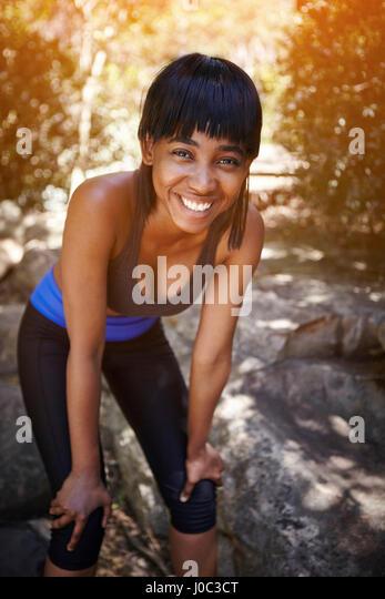 Porträt der jungen Frau im Freien, auf Knien, lächelnd die Hände Stockbild