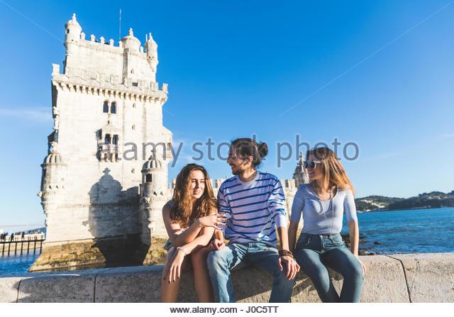 Drei Freunde, sitzen auf der Mauer auf dem Seeweg, Belem Turm im Hintergrund, Lissabon, Portugal Stockbild