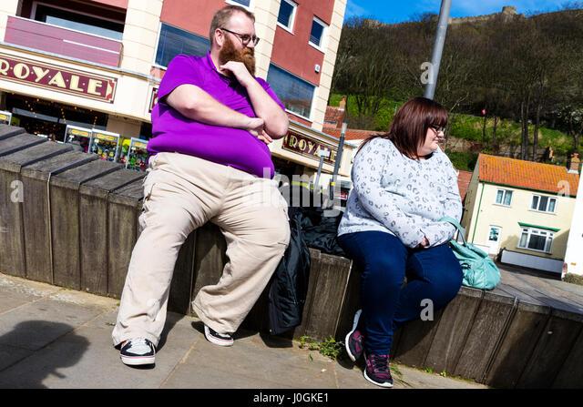 Fettleibigkeit in UK fette Leute saßen ruhenden dazwischen Mahlzeiten Fett Fett Mittelbauch Dicke Bäuche Stockbild