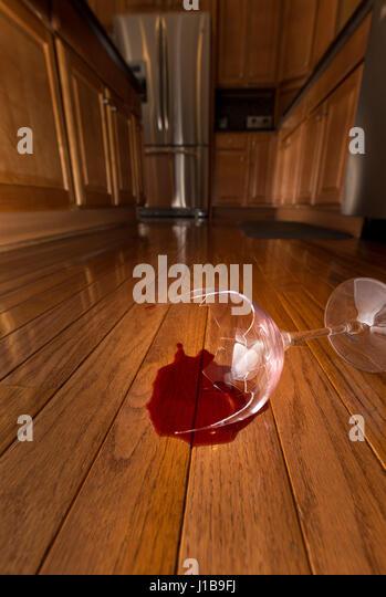 Konzept der inländischen Störung zu Hause mit Wein Glasscherben am Boden der modernen Küche Stockbild