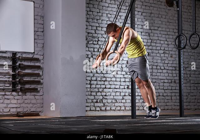Junger sportlicher Mann in der Sportswear-Ausbildung am Kreuz fit Fitness-Studio mit Ringen gegen Mauer. Sportler Stockbild