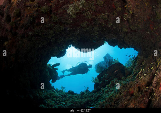 Taucher schwimmt in Richtung Öffnung im Riff. Stockbild