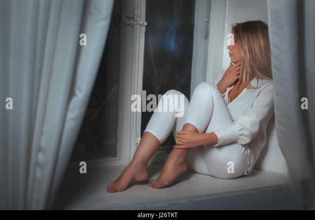 Mädchen Träume am Fenster zu sitzen, war sie traurig. Stockbild