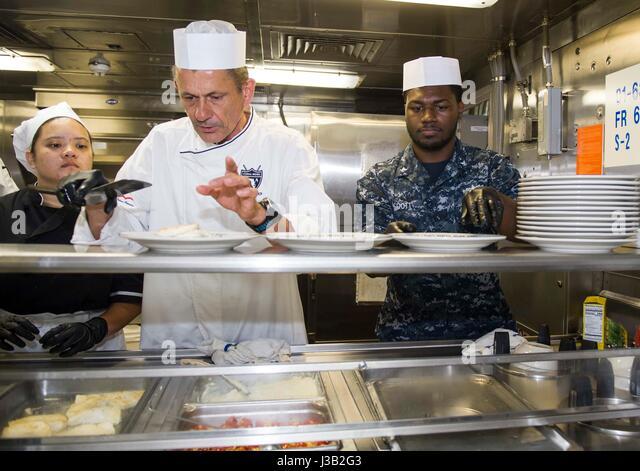 Bereiten Sie Starkoch Udo Müller, Zentrum, neben der US Navy Matrosen Mittagessen an Bord der amphibischen Stockbild