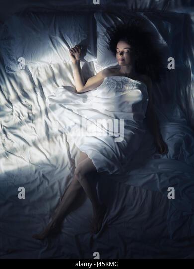 Künstlerische Overhead Foto einer jungen Frau, die alleine schlafen im Bett in der Nacht im dunklen Schlafzimmer Stockbild