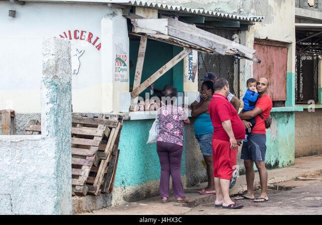 Kubaner, die Schlange, um aus einem Geschäft in einer Seitenstraße in Havanna zu kaufen Stockbild