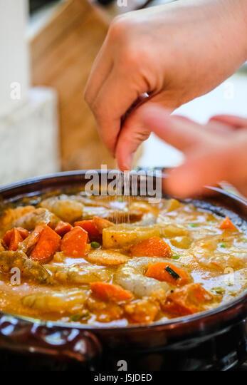 Ein vertikales Bild des weiblichen Händen Prise Salz in einen Topf mit Meeresfrüchten auf dem Herd Stockbild