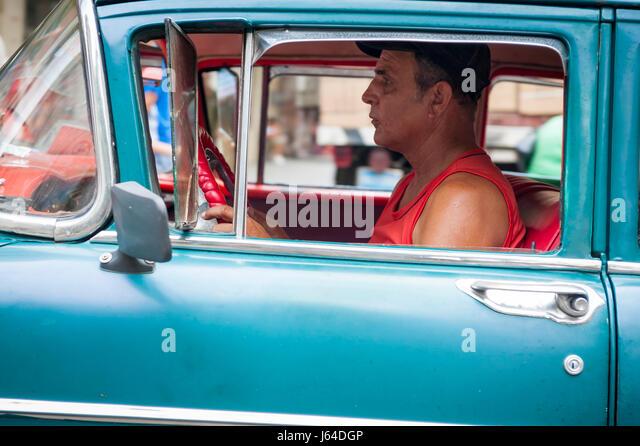 Havanna, Kuba - Juni 2011: Ein kubanischer Taxifahrer lenkt seinen amerikanischen Oldtimer entlang einer Straße Stockbild