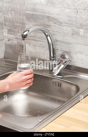 Nahaufnahme von weiblicher Hand hält Trinkglas unter fließendem Leitungswasser gegen Küchenspüle Stockbild