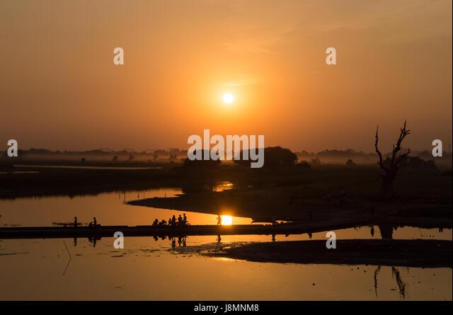 Silhouetten von Menschen auf Taungthaman See bei Sonnenuntergang, in Amarapura, Mandalay, Myanmar Stockbild