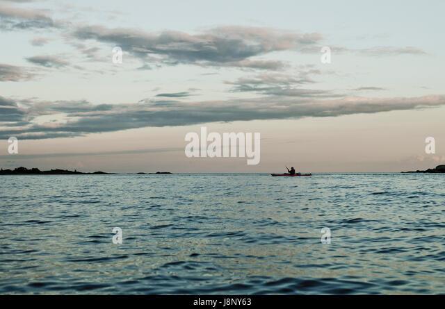 Seelandschaft mit Silhouette des Mannes im Ruderboot Stockbild