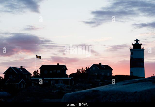 Kleine Häuser und Leuchtturm Meer bei Sonnenuntergang Stockbild