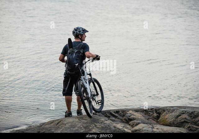 Mann mit Fahrrad tatenlos See Stockbild