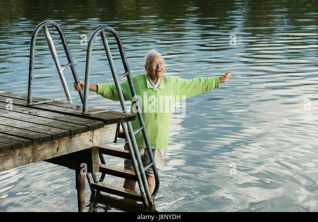 Frau von Pier, waten im Wasser Stockbild