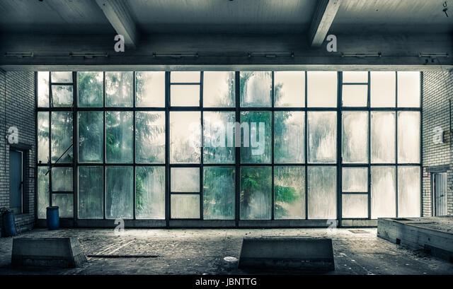 Die Aussicht aus einer alten, verlassenen Fabrik auf der Innenseite mit schönen Fensterlicht Stockbild