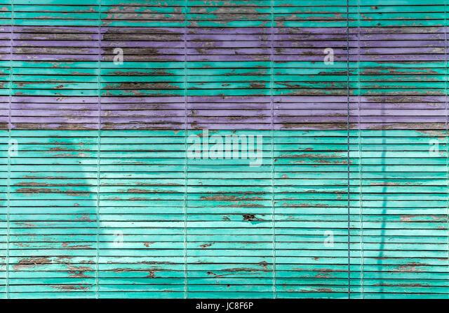 Grün und lila horizontale Jalousien Lamellen mit abblätternde Farbe Stockbild