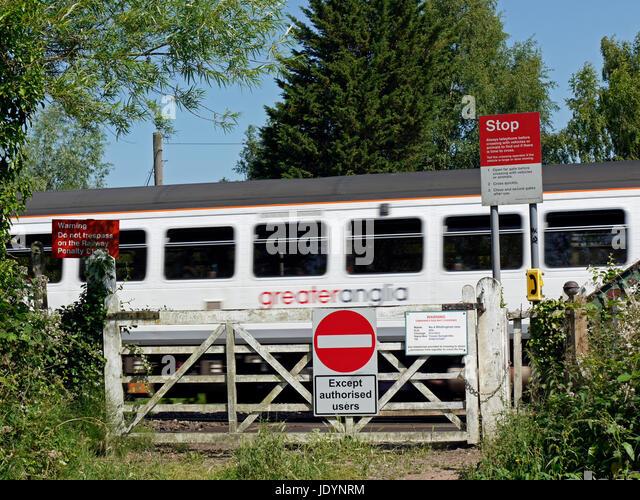 Eine größere Anglia Regionalzug überqueren eine alte Bahnübergang mit Warnschildern östlich Stockbild
