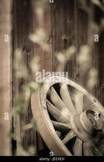Altes Wagenrad ländliche Gebäude Außenwand. Rustikale Holz Nostalgie-Objekt. Stockbild