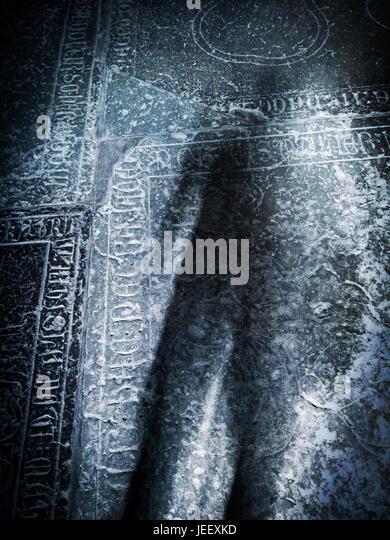 Gruselige Schatten auf alten Grabstein in der Kirche. Konzept des Todes, Kriminalität und Horror. Stockbild