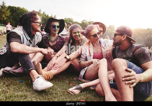 Freunde sitzen auf dem Rasen beim Musikfestival Stockbild