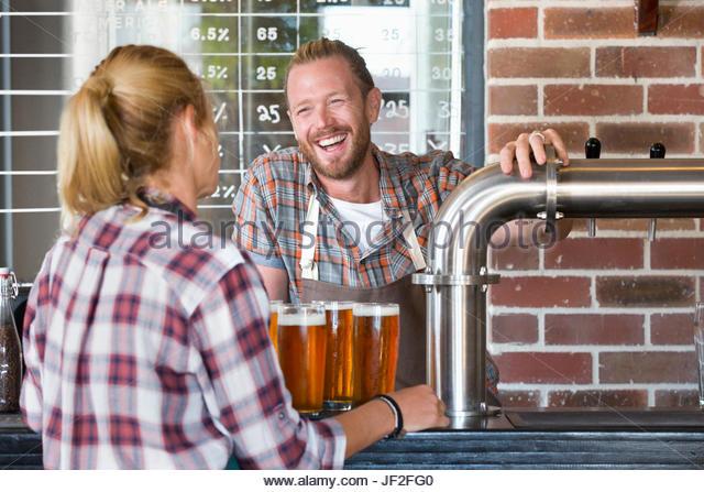 Barkeeper im Pub Gießen Pint Bier für Kellnerin im Pub Stockbild