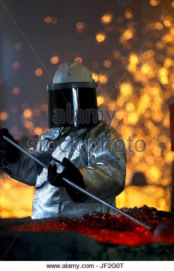 Arbeiter In Schutzkleidung, die Überprüfung von geschmolzenen Metalls In Gießerei Stockbild