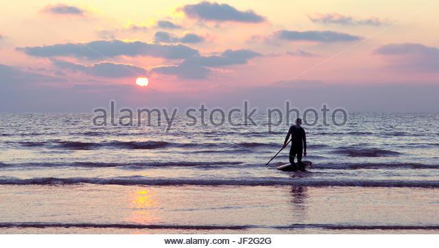Silhouette von männlichen Stand Up Paddel-Boarder am Ufer bei Sonnenuntergang Stockbild