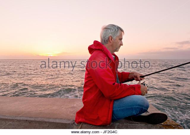 Reifer Mann Meer Angeln vom Steg Sonnenuntergang im Hintergrund Stockbild