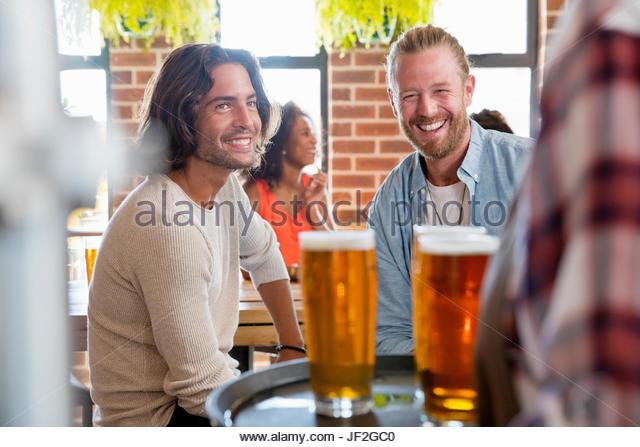 Kellnerin serviert zwei männlichen Freunden treffen für Getränke In der Bar Stockbild