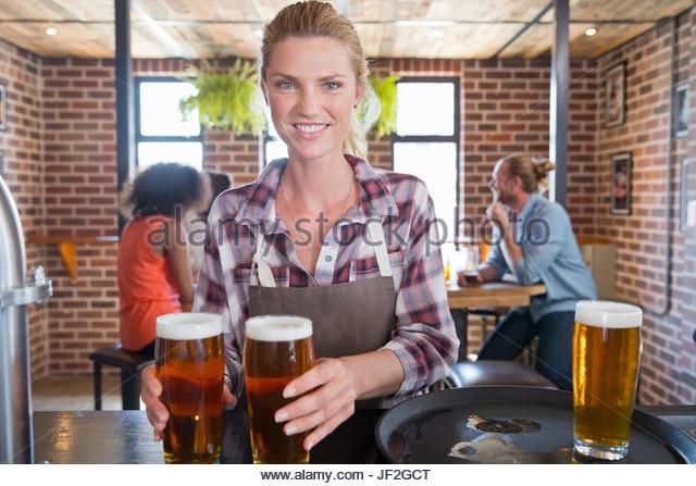 Porträt der Kellnerin Zähler In Bar mit Tablett mit Getränken Stockbild