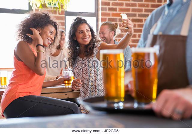 Zwei Freundinnen In Bar posiert für Selfie auf Handy Stockbild