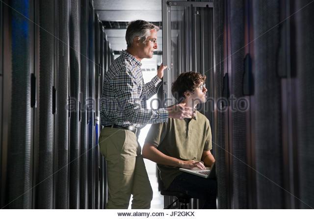 Zwei Techniker mit Laptop arbeiten im sicheren Rechenzentrum Stockbild