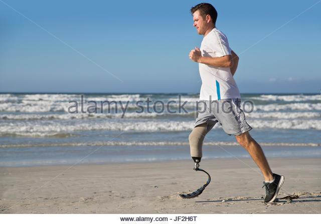 Mann mit Messer Stil künstliches Bein Strand entlang laufen Stockbild