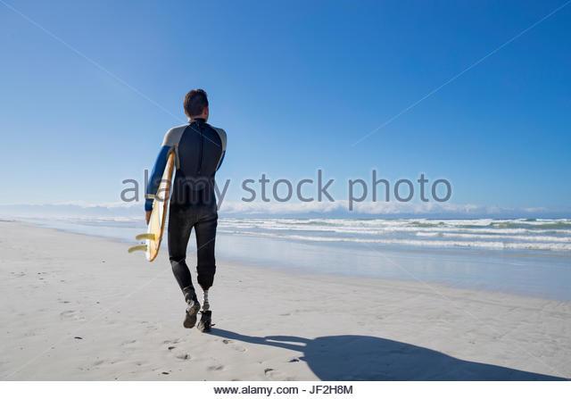 Surfer mit künstlichem Bein stehen am Strand Stockbild