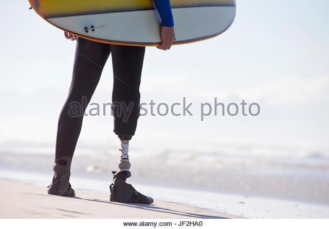 Nahaufnahme von Surfer mit künstlichem Bein stehen am Strand Stockbild
