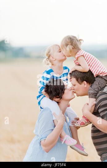 Familie mit zwei Kindern küssen im Feld Stockbild