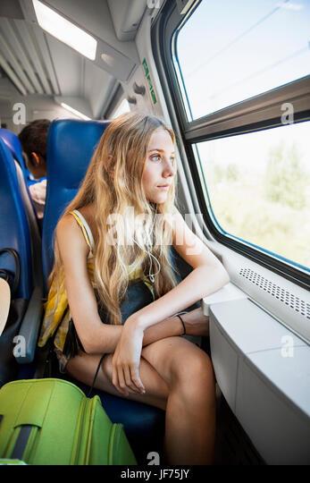 Junge Frau, die durch Fenster in Zug Stockbild