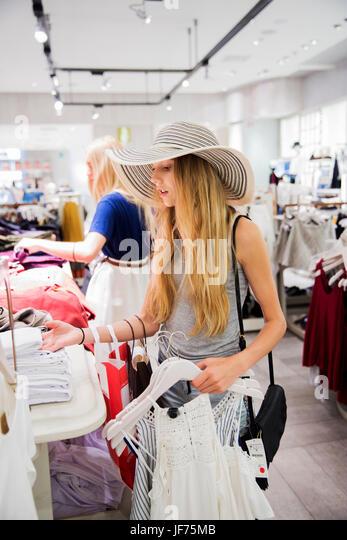 Junge Frau, die Wahl der Kleidung im Shop Stockbild